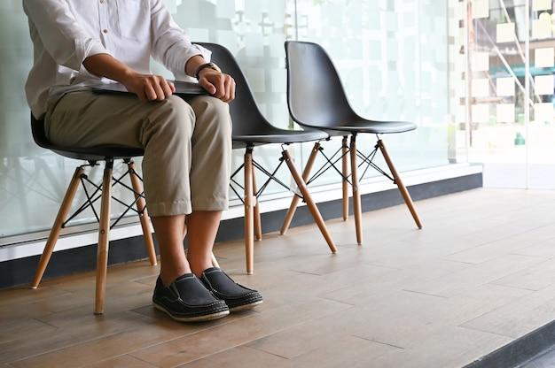 Tiro recortado hombre esperando entrevista sentado en silla. Foto Premium