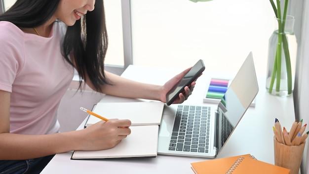 Tiro recortado joven creativa escribiendo en el cuaderno y leyendo en el teléfono inteligente. Foto Premium