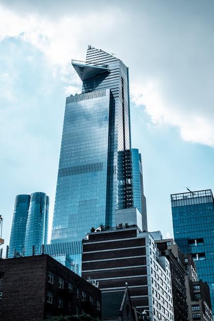 Tiro vertical de ángulo bajo de modernos edificios de negocios de vidrio tocando el cielo Foto gratis