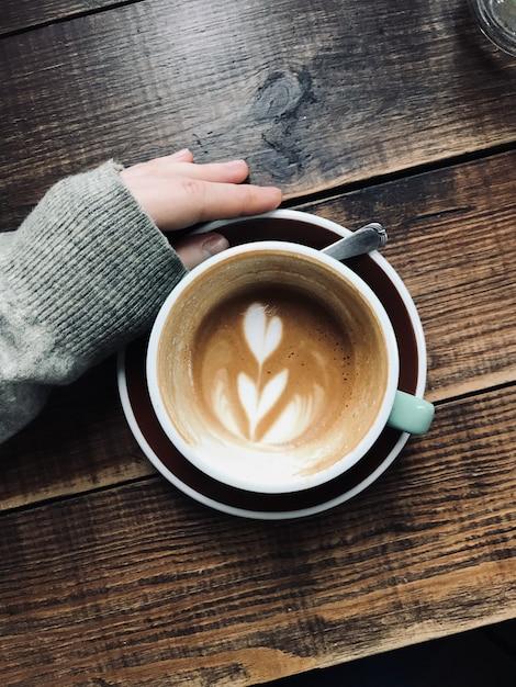 Tiro vertical de arriba de la mano de una persona cerca del café con leche en una superficie de madera Foto gratis