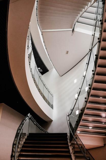 Tiro vertical de escaleras de hormigón dentro de un edificio con luces encendidas Foto gratis