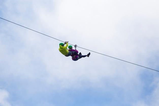 Tirolesa turística aventurera contra el cielo nublado Foto gratis