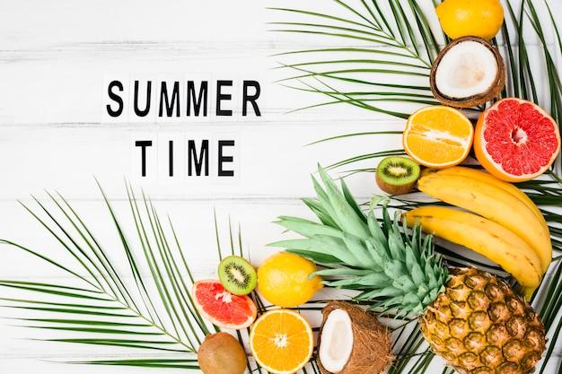 Título de horario de verano entre hojas de plantas cerca de frutas tropicales. Foto gratis