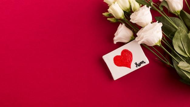 Título de mamá y corazón sobre lienzo cerca de ramo de flores. Foto gratis