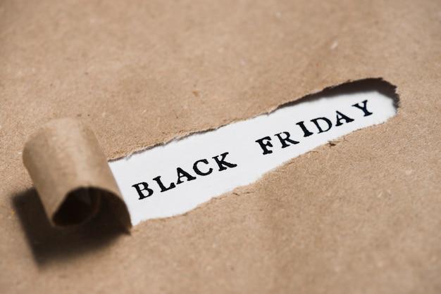 Titulo de viernes negro entre papel artesanal. Foto gratis