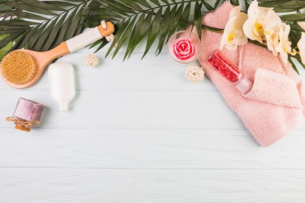 Toalla; botella de sal; cepillo; flores y hojas sobre fondo de madera. Foto gratis