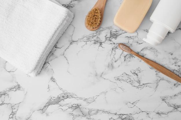 Toalla; cepillo; jabonera y botella cosmética en superficie de mármol. Foto gratis