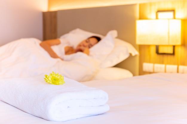 Toalla con flor en cama en habitación de hotel con mujer durmiendo Foto Premium