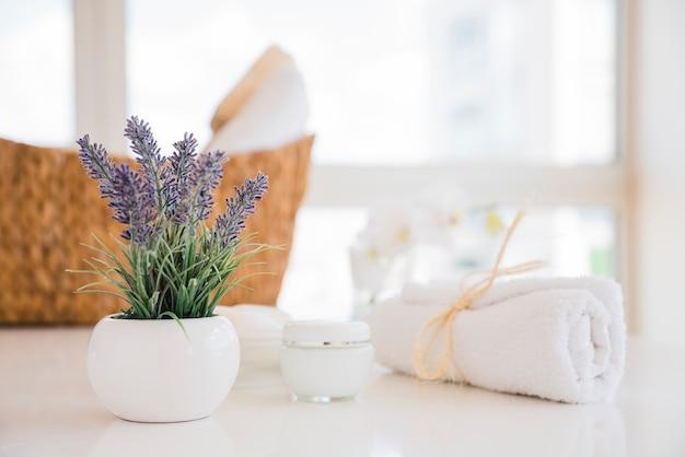 Toalla y flores de lavanda en mesa blanca con crema Foto gratis