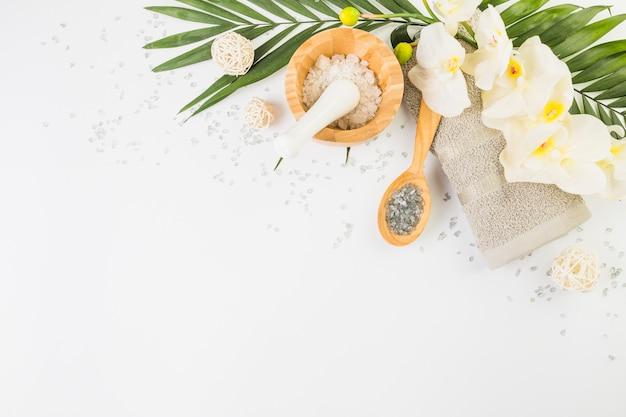 Toalla; sal del himalaya; flores falsas y hojas sobre fondo blanco Foto gratis