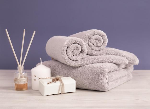 Toallas de rizo grises enrolladas y dobladas con jabón y velas contra la pared lila Foto Premium