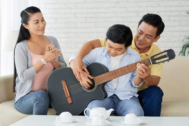 Tocar la guitarra con papá Foto gratis