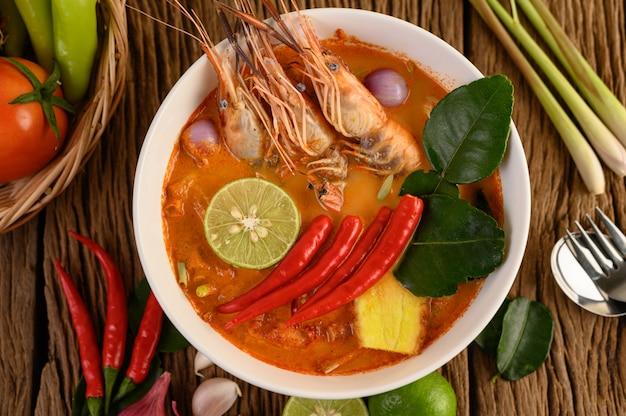 Tom yum kung thai sopa picante de camarones con hierba de limón, limón, galanga y chile en mesa de madera, comida de tailandia Foto gratis