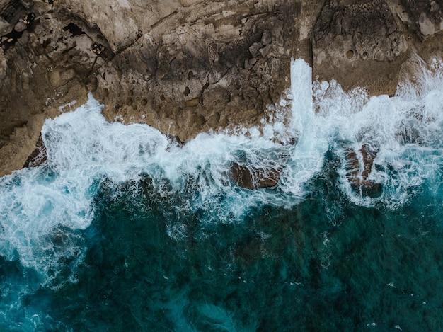 Toma aérea aérea de los hermosos acantilados oceánicos y el agua salpicando sobre ellos Foto gratis