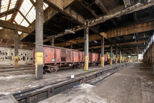 Toma interior de un antiguo almacén con viejos trenes almacenados en su interior Foto gratis