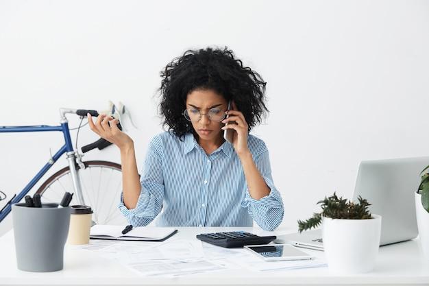 Toma interior de la empresaria afroamericana haciendo llamadas telefónicas Foto gratis
