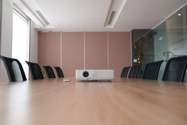 Toma panorámica de una oficina vacía con el proyector en medio de un escritorio de conferencia Foto gratis