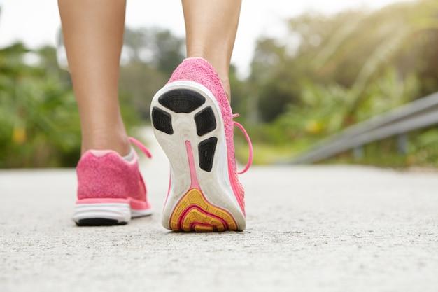 Toma trasera recortada de chica atlética con zapatillas rosas mientras camina o trota en la acera al aire libre. basculador de mujer con hermosas piernas en forma haciendo ejercicio. Foto gratis