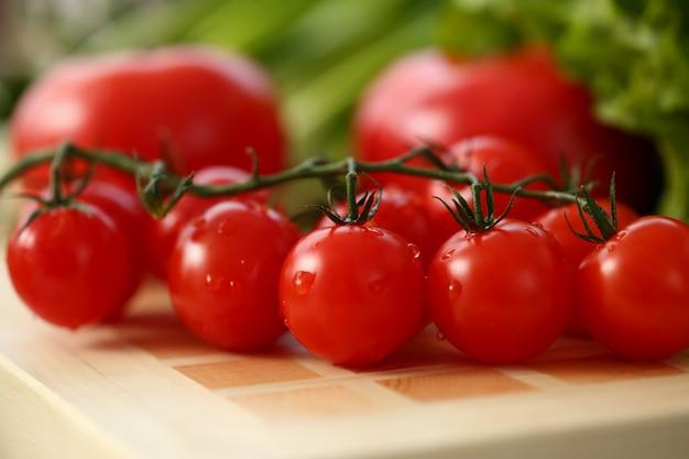 Los tomates cherry se encuentran en una tabla de cortar en la cocina en el contexto del concepto de alimentación saludable verde Foto Premium