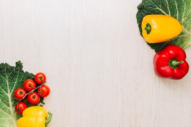 Tomates cherry y pimientos en hoja de col verde en la esquina de la superficie de madera con espacio de copia de texto Foto gratis