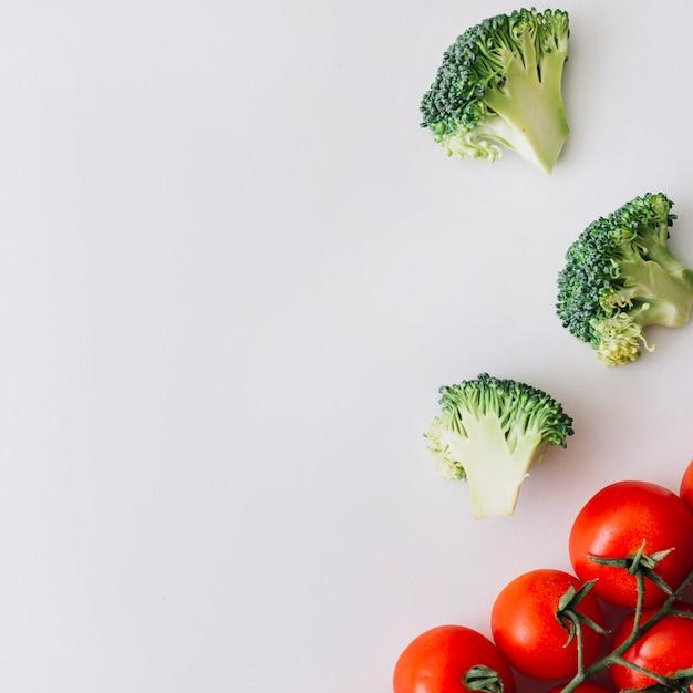 Tomates cherry rojos y rodajas de brócolis frescas sobre fondo blanco Foto gratis