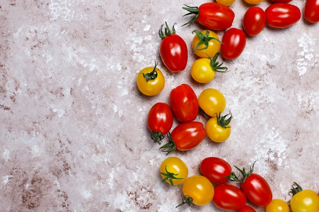 Tomates cherry de varios colores, tomates cherry amarillos y rojos sobre fondo claro Foto gratis