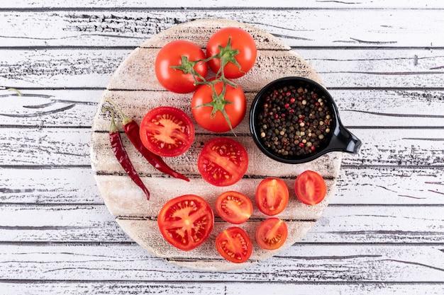 Tomates completos y medios en tablero blanco seco pimiento rojo picante aislado y pimienta negra en polvo en un tazón negro sobre superficie de madera blanca Foto gratis