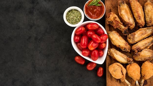 Tomates y especias cerca de pollo asado Foto gratis