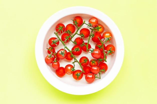 Tomates frescos en un tazón de agua en verde. Foto Premium