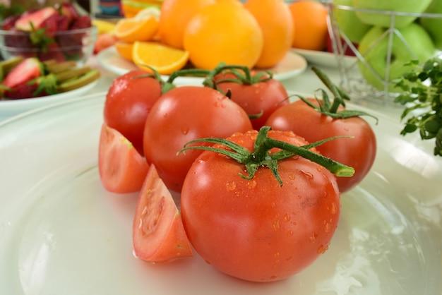 Tomates rojos frescos con gotas de agua sobre la piel del tomate. mezclar frutas. frutas frescas cerca de ti. Foto Premium