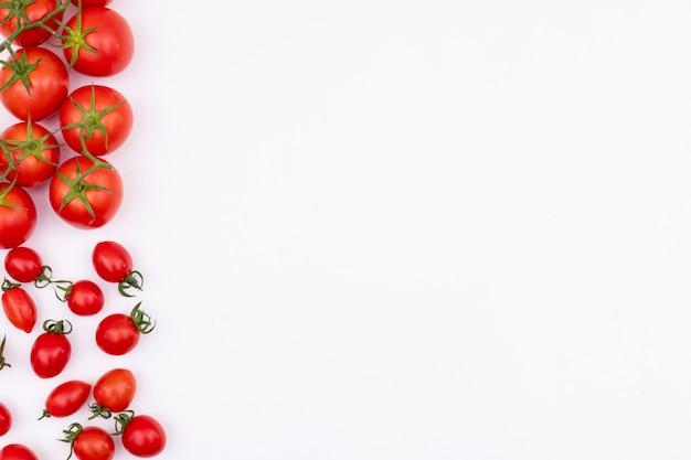 Tomates rojos frescos a la izquierda de la superficie blanca del borde del marco esparcidos tomotoes Foto gratis