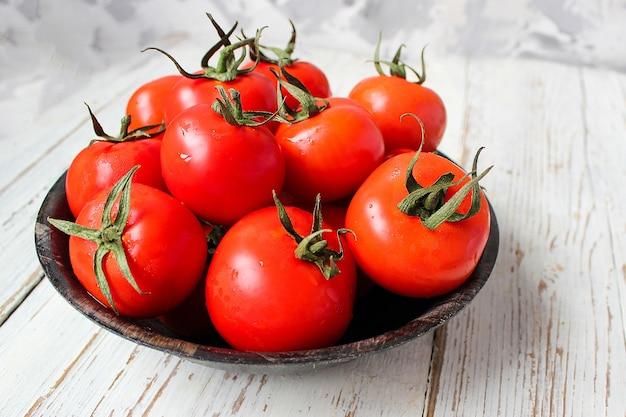 Tomates rojos orgánicos frescos en placa negra en la mesa de madera blanca con pimientos verdes y rojos y pimientos, pimientos verdes, granos de pimienta negra, sal, primer plano, concepto saludable Foto gratis
