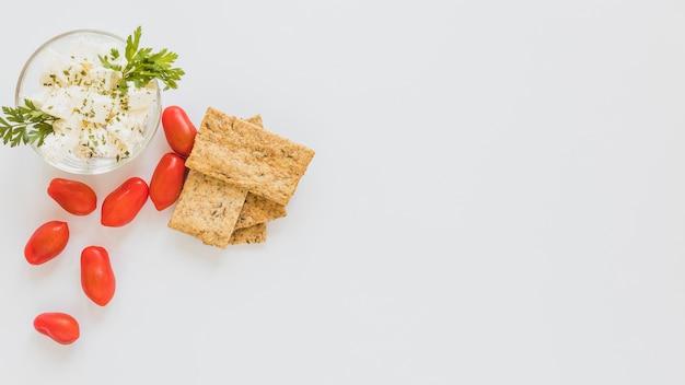 Tomates rojos y pan crujiente con queso tazón sobre fondo blanco Foto gratis