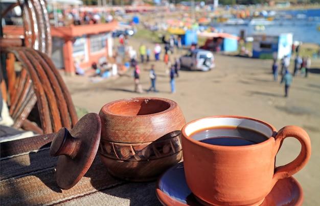 Tome una taza de café en la terraza al aire libre en el piso superior de la cafetería frente al mar Foto Premium