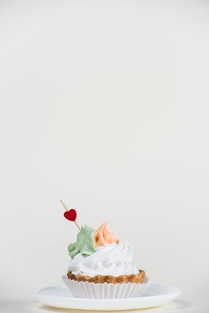 Topper de corazón en cupcake en mesa blanca Foto gratis
