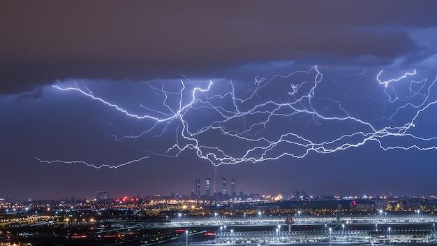 Tormenta eléctrica descargando rayos en la ciudad Foto Premium