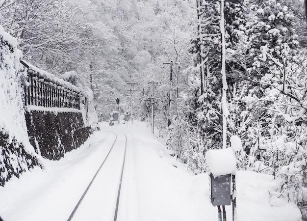Tormenta de nieve con poca visibilidad en las vías del tren. temporada de invierno en la ciudad de toyama, japón. Foto Premium