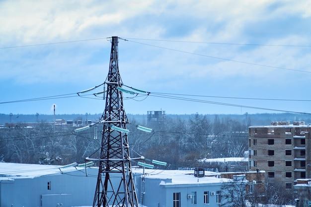 Torre de línea de transmisión de energía con aislantes de alto voltaje cubiertos de nieve. tiempo de invierno Foto Premium