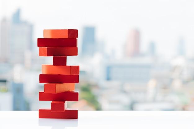 La torre de torre roja de bloques de madera juega con fondos de la ciudad y el cielo. Foto Premium