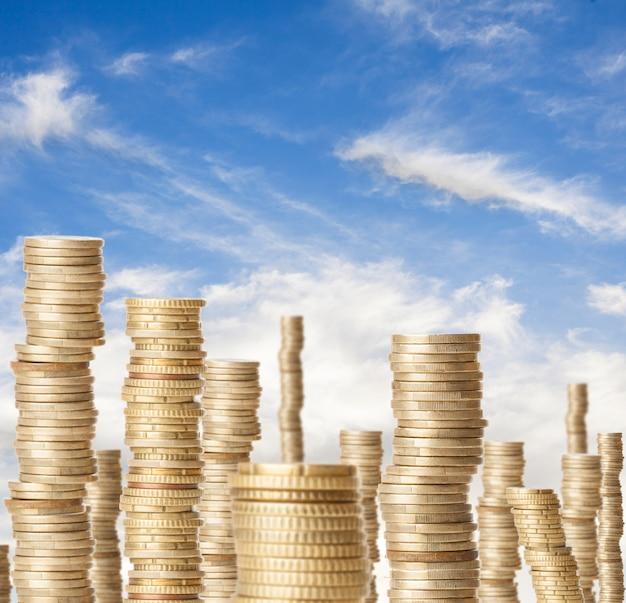 Torres altas de moneda que representa la riqueza bajo un cielo azul Foto gratis