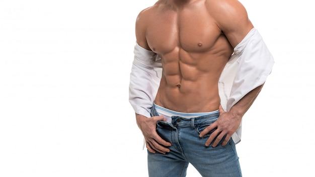Torso masculino con abdominales perfectos. hombre en blue jeans y camisa blanca aislado en blanco. Foto Premium