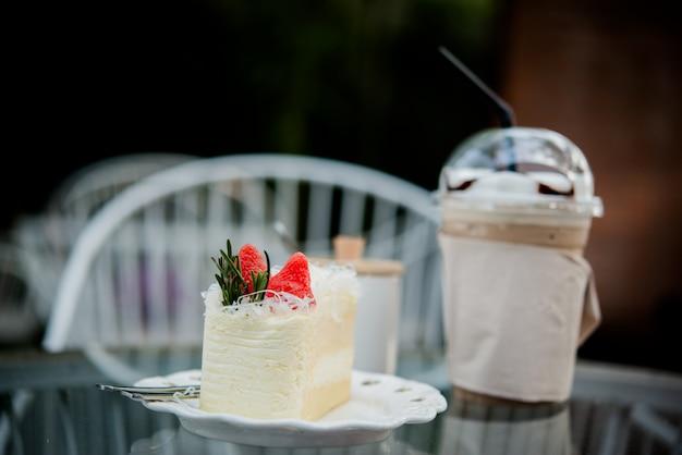 Torta con café con hielo en la mesa en la cafetería Foto gratis