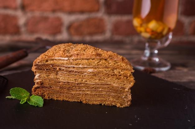 Torta de miel con menta en un plato de piedra en la mesa de madera rústica Foto Premium