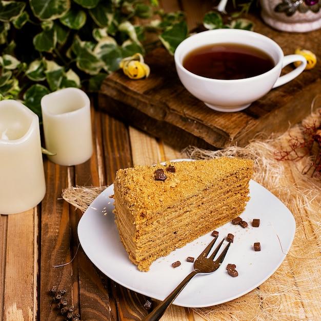 Torta de la miel, rebanada del medovik con una taza de té. Foto gratis