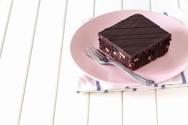 Torta oscura hecha en casa del brownie del vegano del chocolate con el fondo rosado nuts del blanco de la placa. Foto Premium