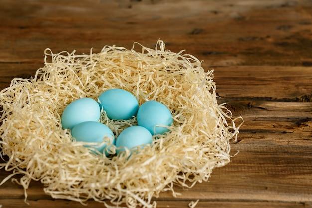 Torta de pascua y huevos coloridos en una tabla de madera. Foto Premium