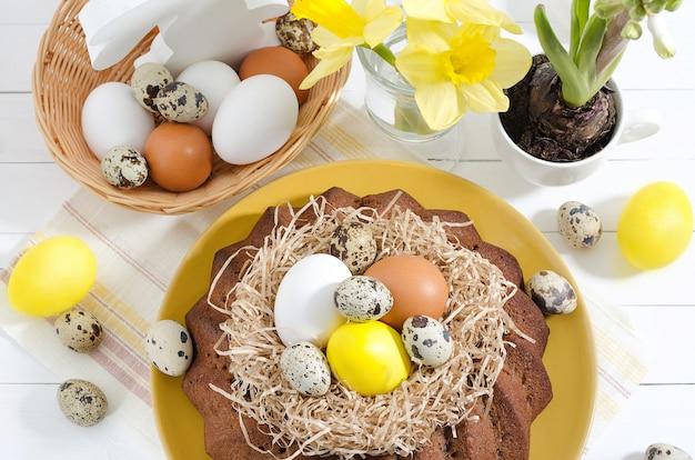 Torta de pascua con huevos teñidos en un nido, narcisos y jacintos en una taza sobre un fondo de madera rústico blanco Foto Premium