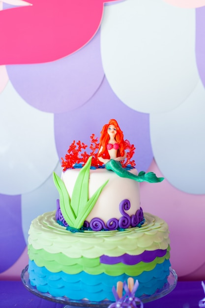 Torta temática de sirena con colas de colores brillantes, conchas y adornos de criaturas marinas Foto Premium