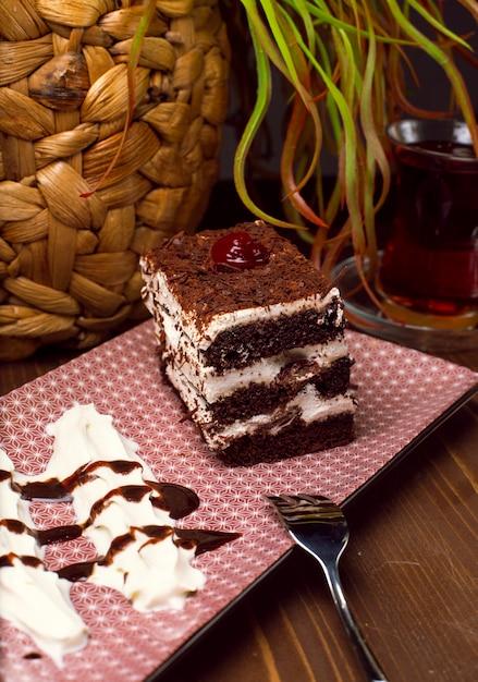Torta de tiramisú en rodajas hecha de chocolate y esponja blanca. un trozo de postre sobre tablas de madera. Foto gratis