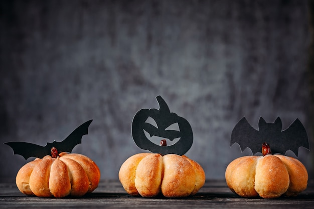 Tortas caseras en forma de calabaza y decoraciones de halloween sobre fondo oscuro Foto Premium